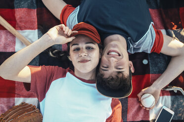 Portrait of smiling young couple with baseball equipment lying on a blanket - RTBF01096