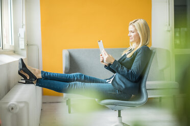 Businesswoman using tablet sitting on chair at the window - MOEF00217