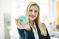 Portrait of smiling businesswoman holding mini globe - MOEF00220