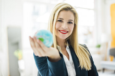 Portrait of smiling businesswoman holding mini globe - MOEF00220