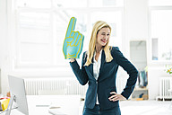 Smiling businesswoman twinkling holding large hand in office - MOEF00223
