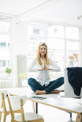 Smiling businesswoman sitting on desk in office practicing yoga - MOEF00229