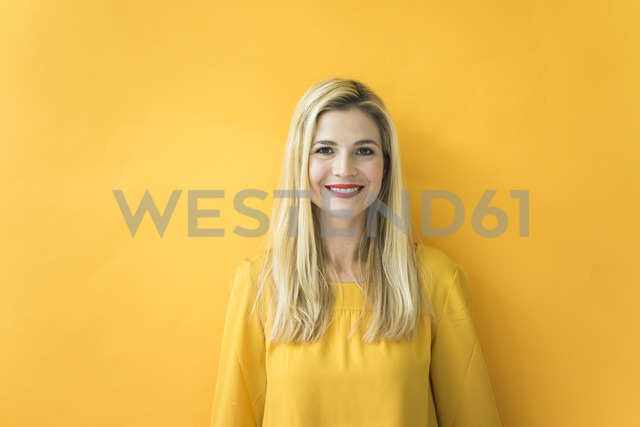 Portrait of smiling woman at yellow wall - MOEF00232 - Robijn Page/Westend61
