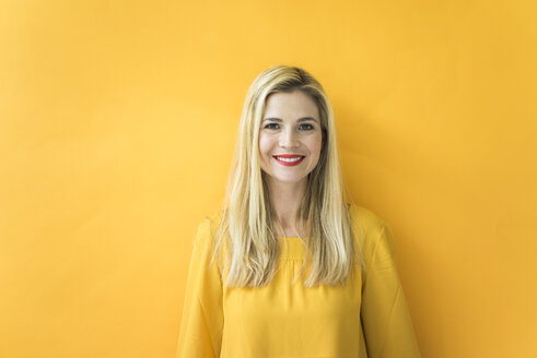 Portrait of smiling woman at yellow wall - MOEF00232