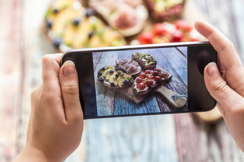 Girl photographing with her smartphone, various sandwiches on chopping board - SARF03399