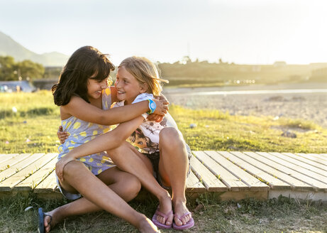 Two best friends sitting on boardwalk hugging each other - MGOF03664