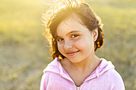Portrait of smiling little girl at backlight - MGOF03682