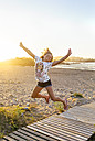 Portrait of smiling girl jumping in the air on the beach - MGOF03688
