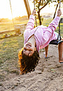 Portrait of little girl sitting on swing leaning back - MGOF03691
