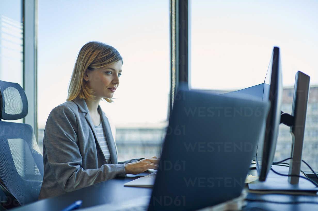 Businesswoman using computer in office - ZEDF00920 - Zeljko Dangubic/Westend61