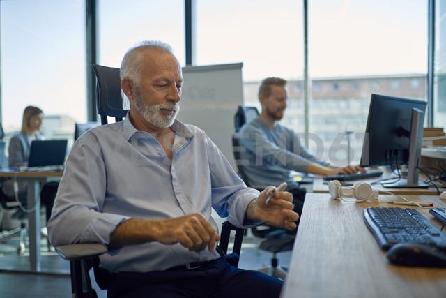 Senior businessman sitting at desk in office - ZEDF00926