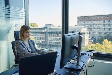 Businesswoman using computer in office - ZEDF00929