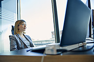 Businesswoman sitting at desk in office - ZEDF00938