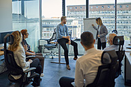 Businesswoman leading a presentation at flip chart in office - ZEDF00944