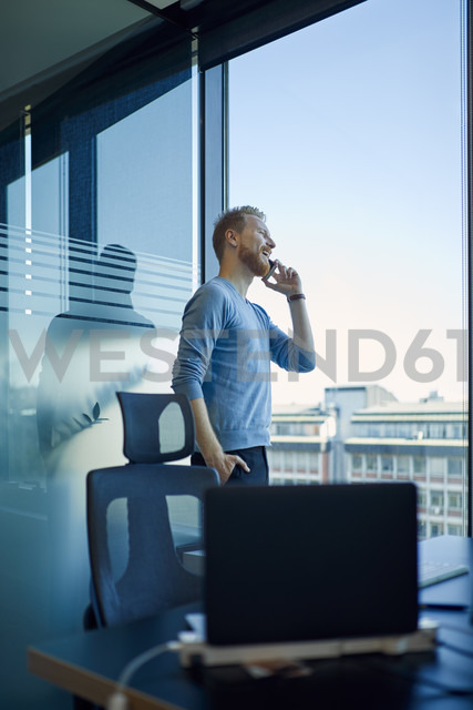 Businessman in office on cell phone at the window - ZEDF00959