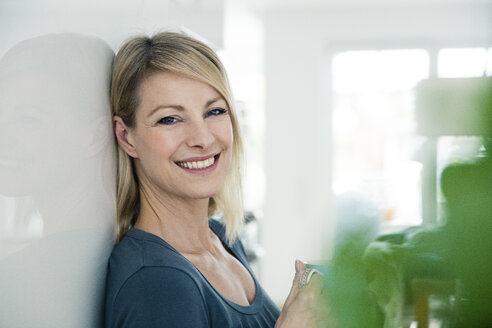 Portrait of smiling blond woman at home - MOEF00244