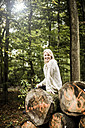 Portrait of happy woman sitting on stack of logs in the forest with tablet - MOEF00253