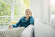 Portrait of happy woman relaxing on couch - MOEF00268