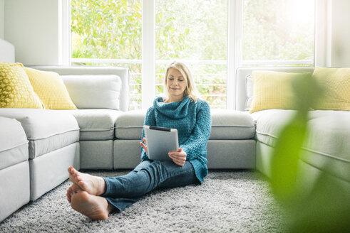 Woman using tablet in living room - MOEF00271