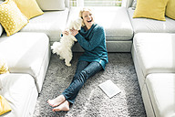 Playful woman with dog in living room - MOEF00274