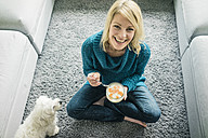 Portrait of happy woman with dog eating fruit yoghurt in living room - MOEF00280