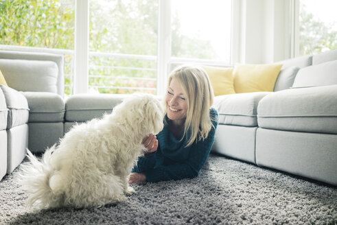 Smiling woman petting her dog in living room - MOEF00283