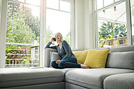Happy woman on the phone on couch - MOEF00289
