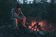 Man sitting at campfire in rural landscape - VPIF00242
