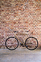 Bicycle at brick wall in office - HAPF02335