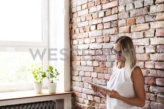 Businesswoman using tablet at brick wall in office - HAPF02341 - HalfPoint/Westend61