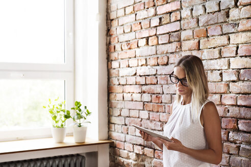 Businesswoman using tablet at brick wall in office - HAPF02341