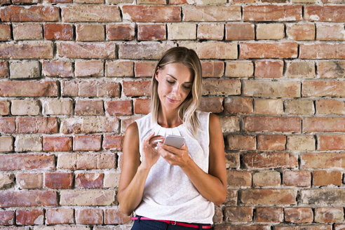 Businesswoman using cell phone at brick wall - HAPF02347