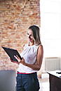 Smiling businesswoman holding clipboard at brick wall in office - HAPF02350