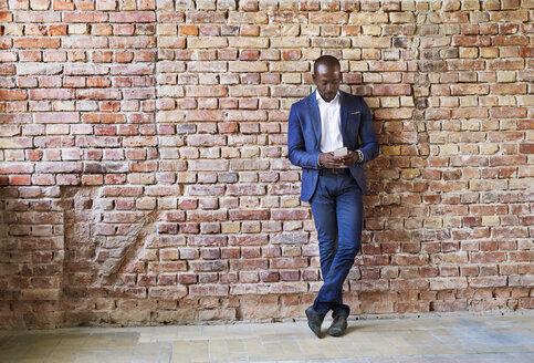 Businessman using cell phone at brick wall - HAPF02353