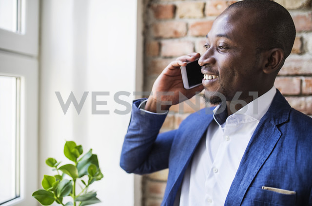 Smiling businessman on cell phone at the window - HAPF02356