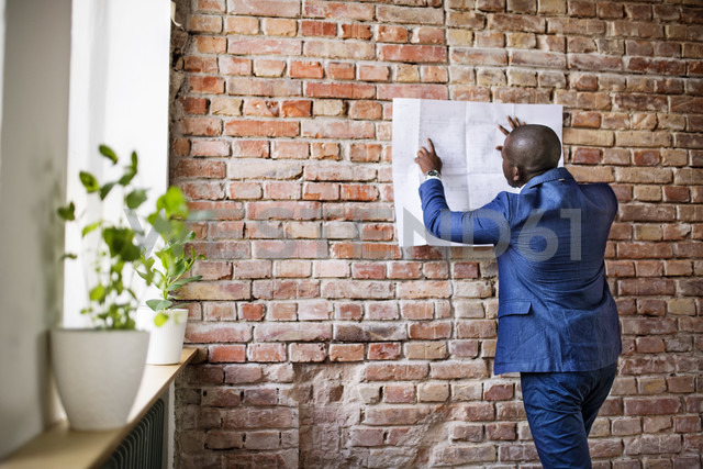 Businessman studying plan at brick wall - HAPF02362