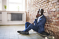 Businessman sitting on longboard listening to music with headphones - HAPF02371