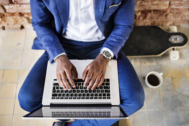 Top view of businessman sitting on longboard using laptop - HAPF02374
