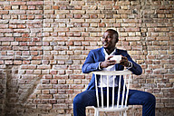 Smiling businessman with cup of coffee sitting on chair at brick wall - HAPF02377