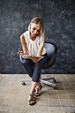 Businesswoman sitting in armchair using tablet - HAPF02383