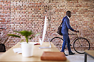 Businessman pushing bicycle in office - HAPF02392