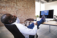 Businessman sitting in office with feet on desk - HAPF02395