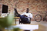 Businessman sitting in office with feet on desk checking cell phone - HAPF02398