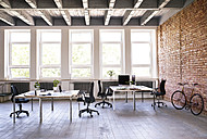 Coworking space and bicycle at brick wall in office - HAPF02413