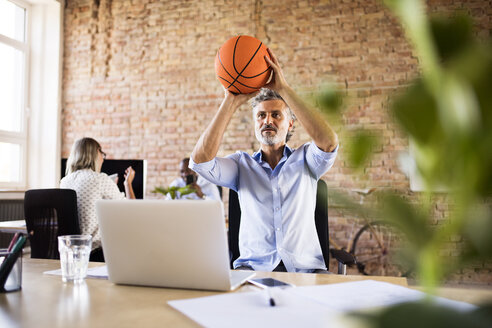 Businessman playing basketball in office with colleagues in background - HAPF02422