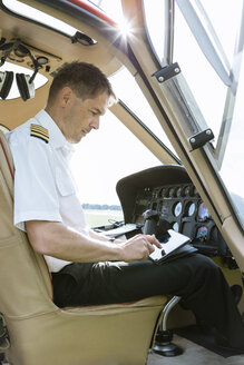 Pilot using tablet in cockpit of a helicopter - OJF00196