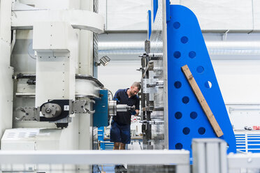 Man working on machine in industrial factory - DIGF03106