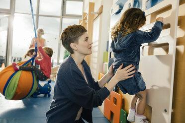 Pre-school teacher helping little girl climbing up a wall - MFF04049