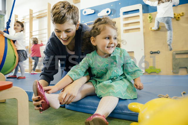 Pre-school teacher helping little girl putting a shoe on - MFF04052 - Mareen Fischinger/Westend61