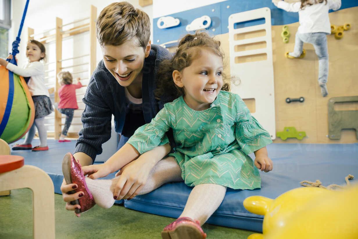 Pre-school teacher helping little girl putting a shoe on - MFF04052 - Mareen Fischinger/Westend61